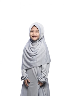 Mała azjatykcia muzułmańska dziewczyna w przesłonie z uśmiech pozycją