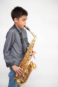Mała azjatykcia muzyk chłopiec bawić się saksofon