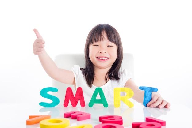 Mała azjatykcia preschool dziewczyna robi angielskiemu słowie jej abecadło zabawką nad białym tłem