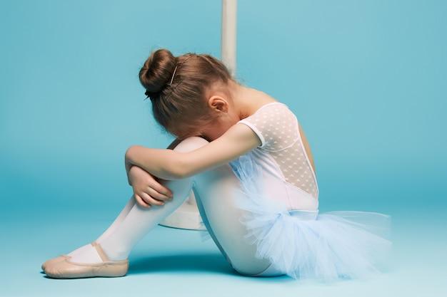 Mała balerina tancerka na niebieską ścianą