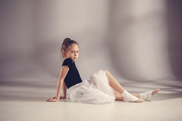 Mała balerina tancerka na szarej ścianie