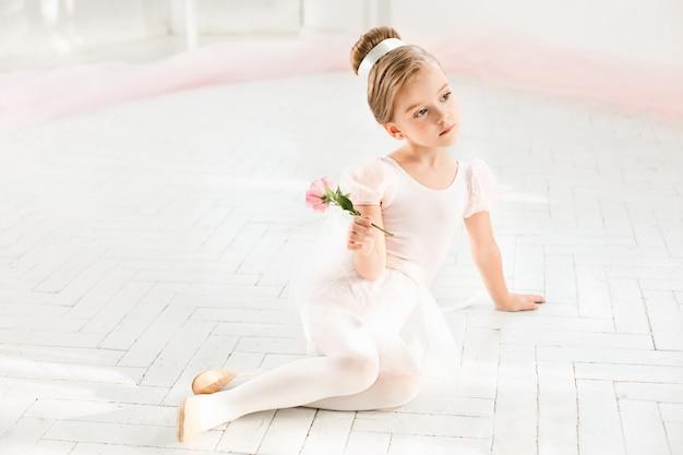 Mała balerina w białej spódniczce baletnicy w klasie na balecie