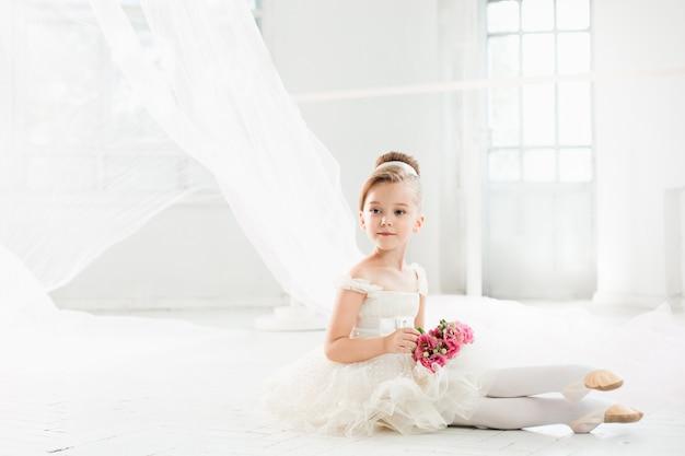 Mała balerina w białej spódniczce baletnicy w klasie w szkole baletowej