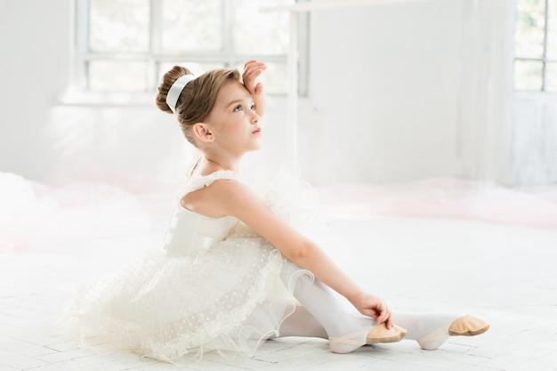 Mała balerina w białej spódniczce tutu w klasie w szkole baletowej