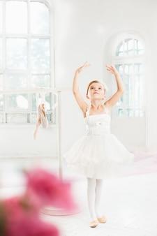 Mała baleriny dziewczyna w spódniczce baletnicy. urocze dziecko tańczy klasyczny balet w białym studiu.