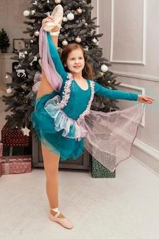 Mała baletnica stoi na jednej nodze na tle choinki