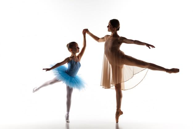 Mała baletnica tańcząca z osobistym nauczycielem baletu w studio tańca