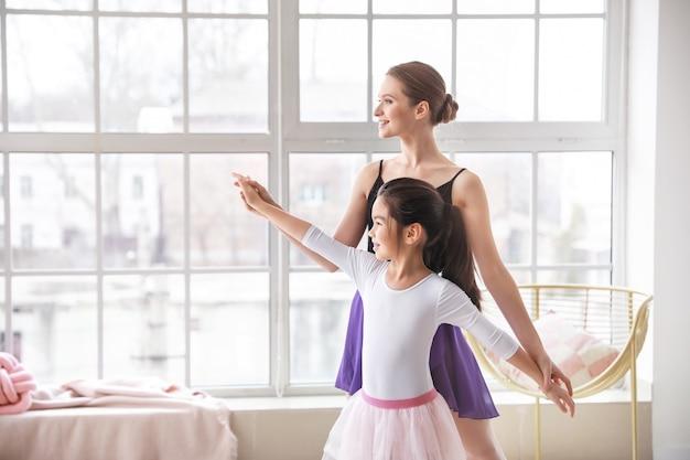 Mała baletnica trenuje z trenerem w studio tańca