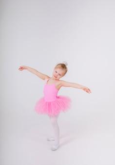 Mała baletnica w różowej sukience ze spódniczką tutu robi pozę na białej ścianie