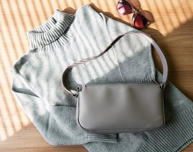 Mała beżowa skórzana torebka i szary damski sweter