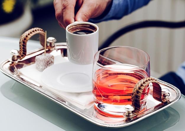 Mała biała filiżanka espresso ze szklanką czerwonego napoju.