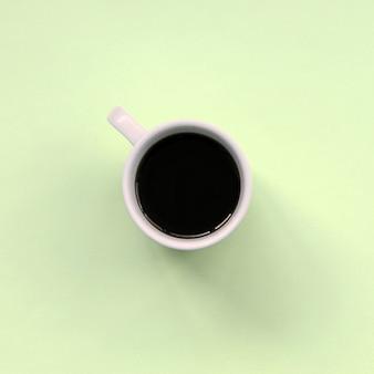 Mała biała filiżanka kawy na fakturze moda pastelowy kolor limonki