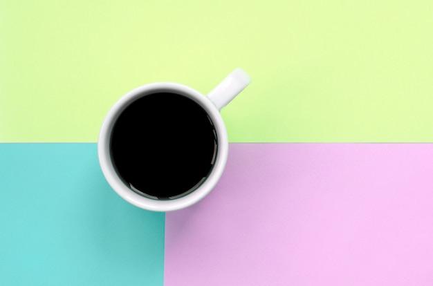 Mała biała filiżanka kawy na fakturze papieru w pastelowych kolorach różu, błękitu i limonki
