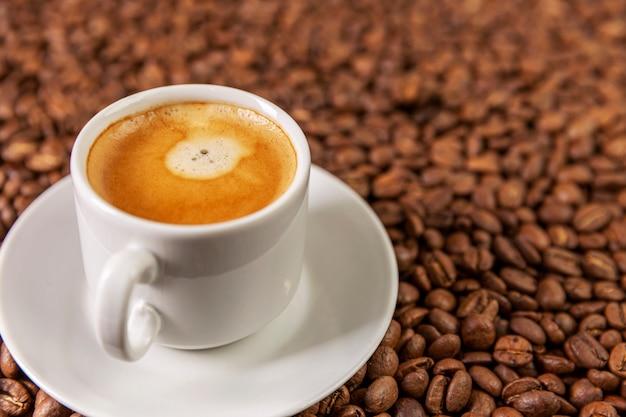 Mała biała filiżanka kawy stoi na ziarnach kawy. pachnąca przyjemność.