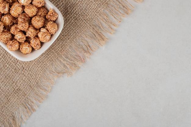 Mała biała miseczka na kawałku materiału nadziewana brązowym kandyzowanym popcornem na marmurowym tle.
