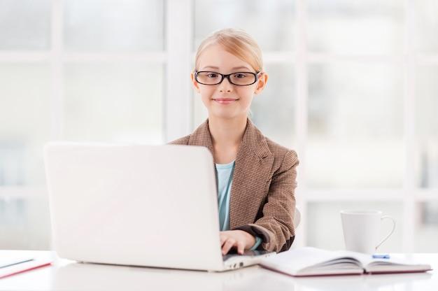 Mała biznesowa dama. śliczna mała dziewczynka w okularach i formalnej odzieży siedzi przy stole i korzysta z laptopa