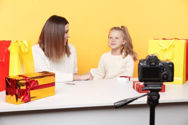 Mała blogerka dziewczyna siedzi z matką i razem nagrywa vloga.