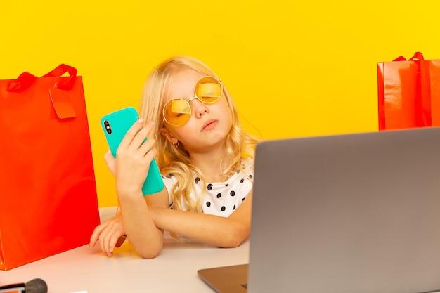 Mała blogerka dziewczyna z niebieskim telefonem, tworzenie wideo dla bloga i obserwujących, siedząc w żółtym studio na białym tle.