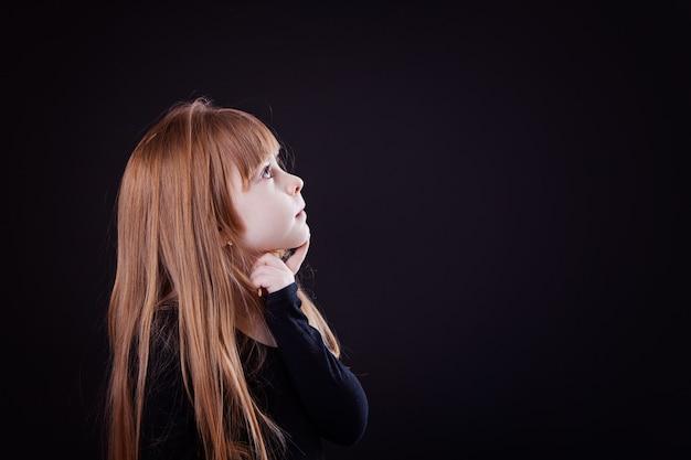 Mała blond dziewczyna patrząc w zamyśleniu w prawo