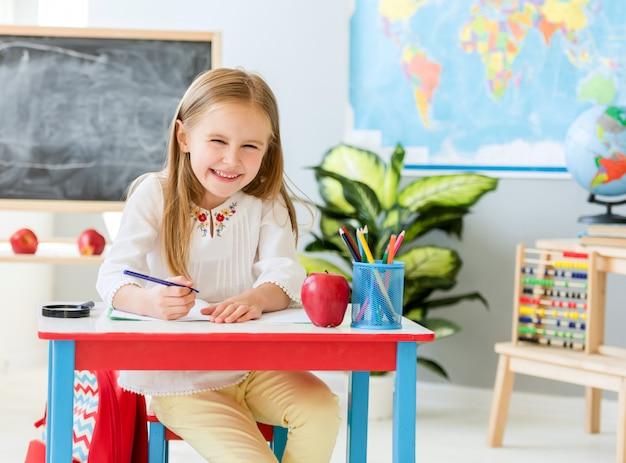 Mała blond dziewczyna siedzi przy białym biurku i pisze w zeszycie, śmiejąc się w klasie szkolnej