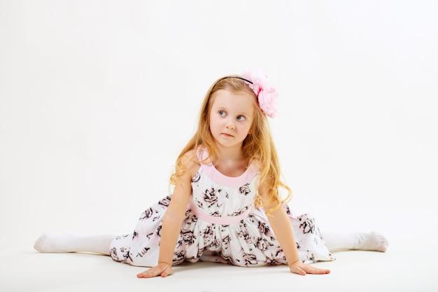 Mała blond dziewczyna w sukience siedzi na sznurku przed białym tle