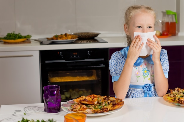 Mała blond dziewczynka je duży talerz pizzy?