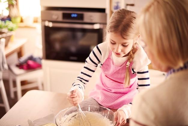 Mała blond dziewczynka miesza ciasto