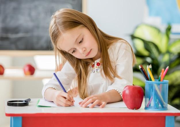 Mała blond dziewczyny writing lekcja w szkolnej sala lekcyjnej