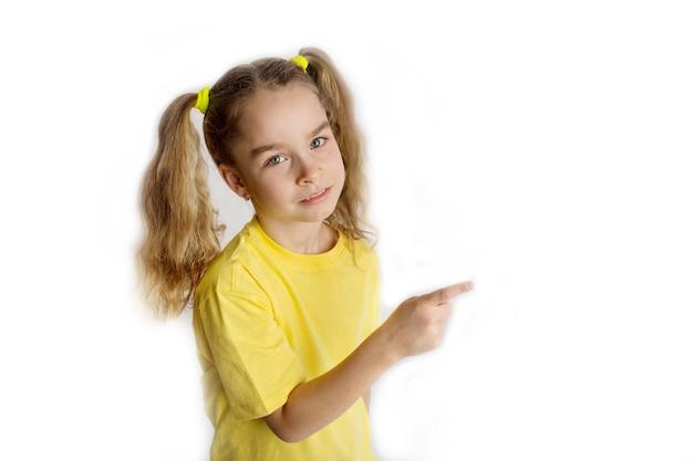 Mała blondynka 8-9 lat w żółtej koszulce robi gesty, podnosząc palce, na białym tle na białym tle portret studio dla dzieci. koncepcja stylu życia dzieciństwa. wysokiej jakości zdjęcie