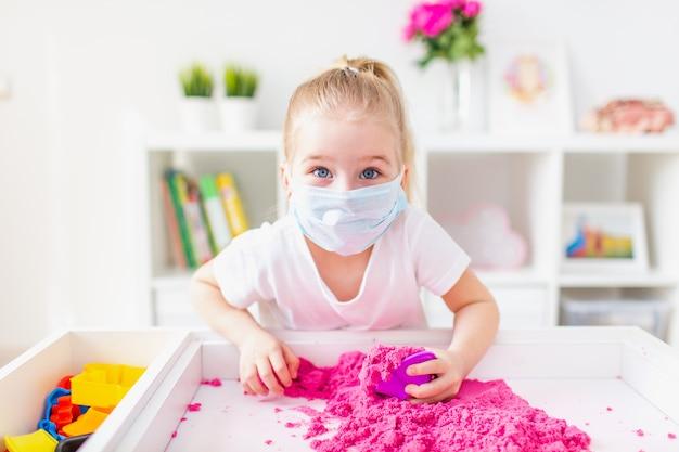 Mała blondynka bawi się w domu różowym piaskiem kinetycznym, ubrana w medyczną ochronną maskę, aby uchronić się przed wirusem