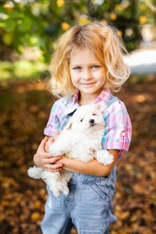 Mała blondynka berbecia dziewczyna z dwa warkoczami bawić się z ładnym białym szczeniakiem