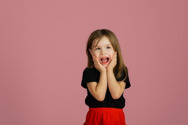 Mała blondynka jest bardzo zaskoczona różową pastelową ścianą. dziecko krzyczące wow trzyma twarz w zdumieniu. copyspace