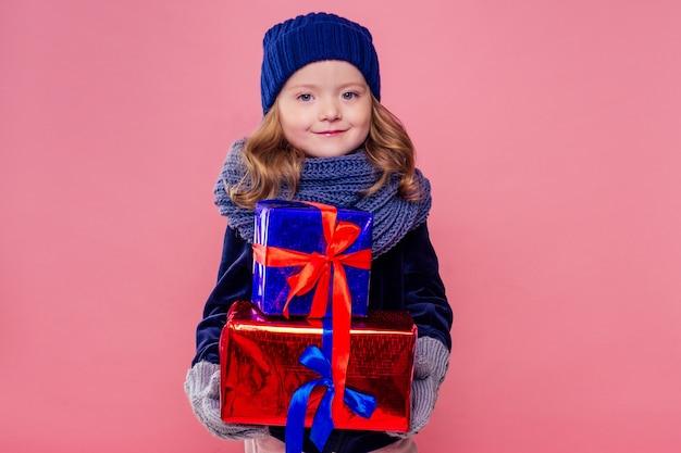 Mała blondynka kręcone fryzury dziewczyna w dzianym różowym kapeluszu, szaliku i rękawiczkach góra prezentów boże narodzenie pudełko różowym tle studio. noworoczny prezent w rękach dziecka płci żeńskiej, która ma życzenie copyspace