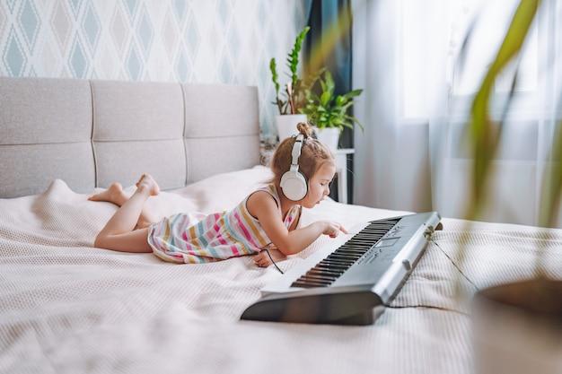 Mała blondynka maluch gra na klasycznym pianinie cyfrowym w domu, leżąc na łóżku.