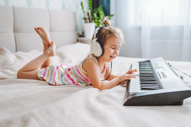 Mała blondynka maluch gra na klasycznym pianinie cyfrowym w domu podczas lekcji online z laptopem.