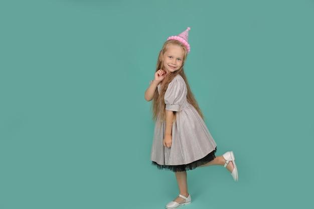 Mała blondynka o niebieskich oczach w szarej sukience w kapeluszu wszystkiego najlepszego z okazji urodzin