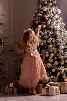 Mała blondynka ozdabia choinkę w pięknym wnętrzu