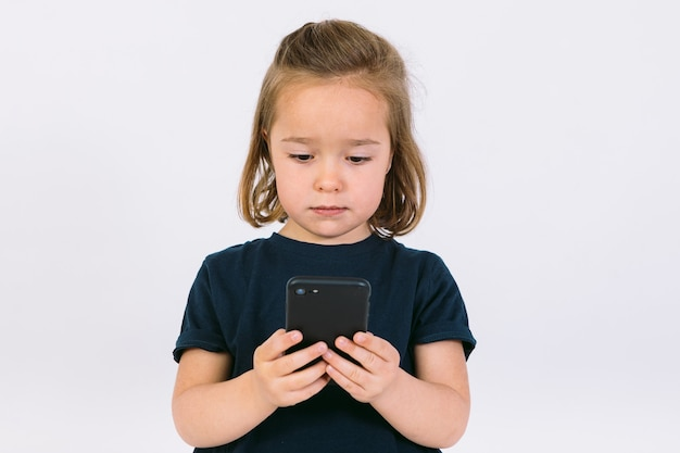 Mała blondynka patrząc na swój telefon komórkowy