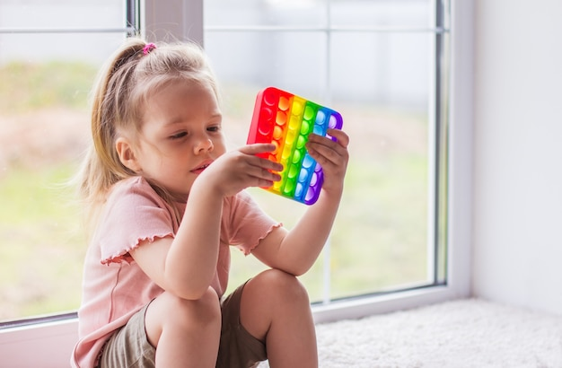 Mała blondynka siedzi przy oknie i bawi się nową, modną zabawką sensoryczną - tęczą pop. antystresowa zabawka olorfula z prostym dołeczkiem. squishy miękkie zabawki bąbelkowe w kolorze tęczy!