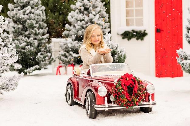 Mała blondynka siedzi w czerwonym dziecięcym kabrioletu w zaśnieżonym lesie świerkowym i łapie płatki śniegu