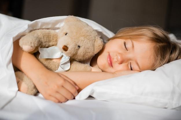 Mała blondynka śpi pod białym kocem w objęciach z misiem