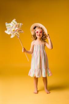 Mała blondynka uśmiecha się w letniej sukience, okularach przeciwsłonecznych, trzymając wiatrak dziecka na żółtej ścianie