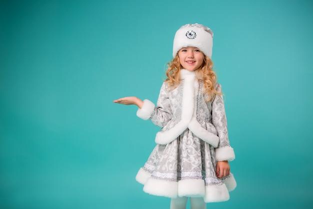 Mała blondynka uśmiecha się w stroju dziewicy śniegu izolować na niebieską ścianą