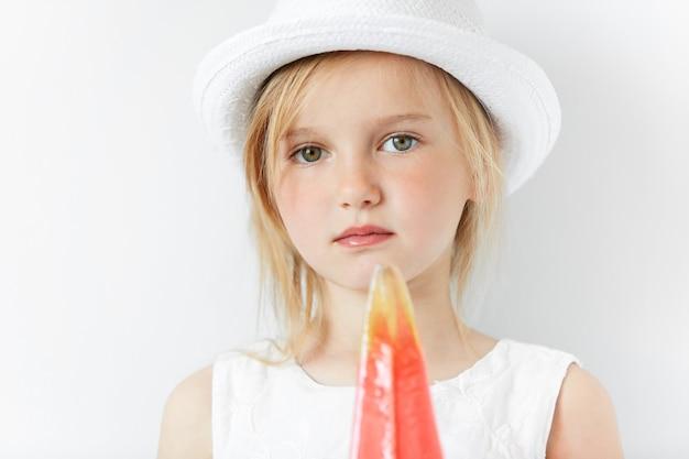 Mała blondynka w białym kapeluszu i trzymając lody na patyku