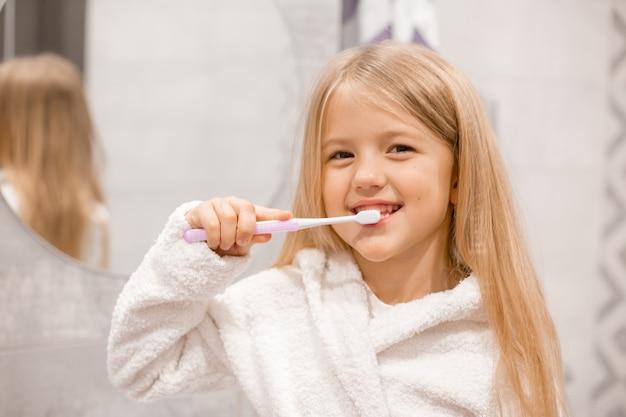 Mała blondynka w białym szlafroku myje zęby przed lustrem w łazience