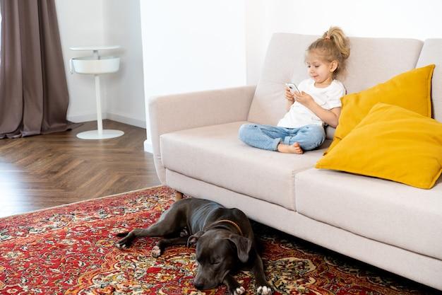 Mała blondynka w domu na kanapie z telefonem komórkowym i dużym psem, dziećmi i gadżetami.