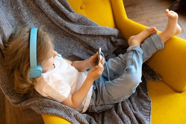 Mała blondynka w domu na krześle słucha muzyki w słuchawkach i gra w smartfonie.