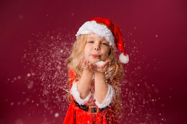 Mała blondynka w garniturze świętego mikołaja wieje śnieg z jej rąk