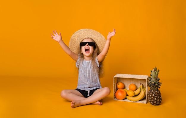 Mała blondynka w okularach przeciwsłonecznych i słomkowym kapeluszu siedzi z koszem owoców na żółtej powierzchni z kopią miejsca