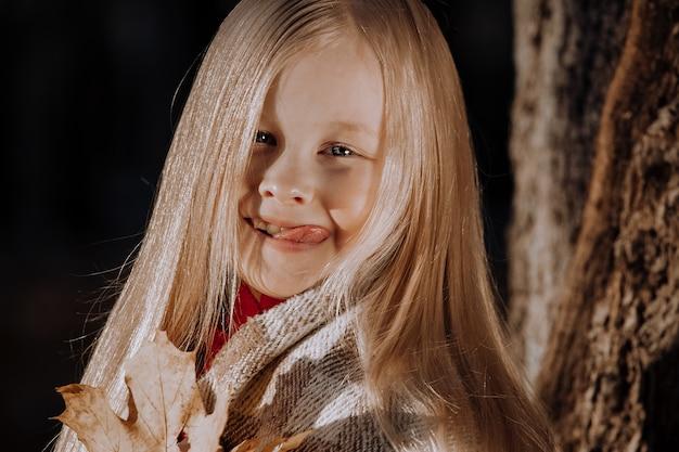 Mała blondynka w plaid bat w parku jesienią